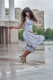 Скача усмехаясь девушка в предпосылке города дождя Стоковая Фотография RF