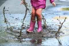 Скачка ребенка внешняя в лужицу в ботинке после дождя стоковая фотография rf