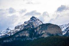 Скалистая гора с белыми облаками Стоковая Фотография