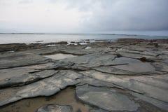 Скалистая линия берега на заходе солнца Стоковое Изображение
