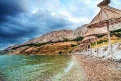 Скалистое costline Адриатического моря с зонтиками, sunbends и чистой водой соломы Ландшафт моря, курорт на береге, каникулы Стоковые Фотографии RF