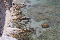 Скалистые берег и кристалл - чистая вода около крепостной стены Alanya, Турции Стоковое Фото