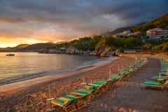 Скалистые берег и loungers на пляже на заходе солнца Стоковая Фотография