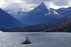 Скалистые горы обрамляют одичалый остров гусыни в национальном парке ледника Стоковая Фотография RF