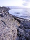 Скалистый берег озера с подъемом солнца Стоковые Фотографии RF