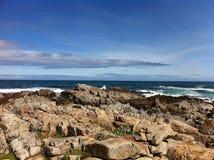 Скалистый вид на океан с ясными голубыми небесами стоковое фото