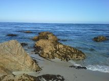 Скалистый пляж на голубом океане с ясным голубым небом Стоковые Фотографии RF