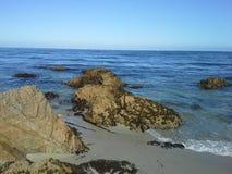 Скалистый пляж на голубом океане с ясным голубым небом Стоковое фото RF