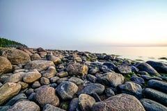 Скалистый пляж на заходе солнца с milky водой Стоковое Изображение