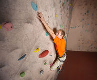 Скалолазание мужского альпиниста практикуя на стене утеса внутри помещения Стоковые Фотографии RF