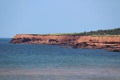 Скалы красных утеса и океанских волн Стоковая Фотография
