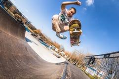 Скейтбордист делает фокус бескостный, высокий прыжок в мини пандусе в skatepark Стоковые Изображения