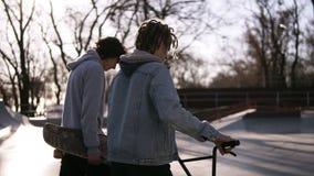 Скейтбордист 2 друзей и всадник bmx идут совместно в парк конька города Друзья связывают в коньке акции видеоматериалы