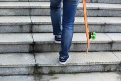 Скейтбордист идя вверх с скейтбордом Стоковое Фото