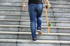 Скейтбордист идя вверх с скейтбордом Стоковые Фото