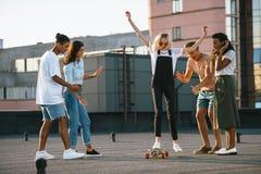 Скейтборд катания девушки на крыше Стоковые Изображения
