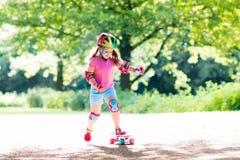 Скейтборд катания ребенка в парке лета Стоковая Фотография