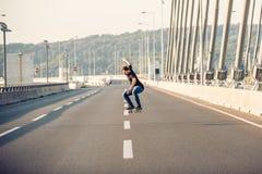 Скейтбордист ехать конек и делая скачки на bri дороги города Стоковые Фото