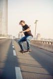 Скейтбордист ехать конек и делая скачки на bri дороги города Стоковое Фото