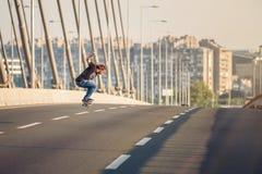 Скейтбордист ехать конек и делая скачки на bri дороги города Стоковые Изображения RF