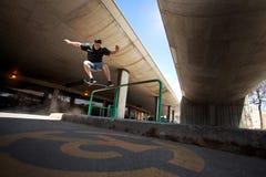 Скейтбордист делая нечестный фокус молотилки на рельсе Стоковые Фото