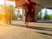 Скейтбордист силуэта скача в город Стоковые Изображения