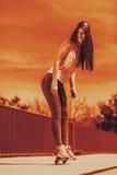 Скейтборд катания конькобежца девочка-подростка на улице Стоковое Фото