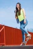 Скейтборд катания конькобежца девочка-подростка на улице Стоковое Изображение