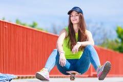 Скейтборд катания конькобежца девочка-подростка на улице Стоковая Фотография