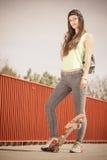 Скейтборд катания конькобежца девочка-подростка на улице Стоковые Изображения
