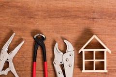 Скелет деревянного дома с инструментом для проблемы починки на деревянной предпосылке стоковые фотографии rf