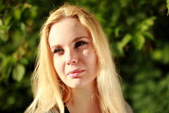 Скептичная блондинка в солнечном лесе, портрет конца-вверх Стоковые Изображения