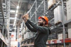 Складируйте менеджер проверяя его инвентарь в большом складе Стоковое Фото