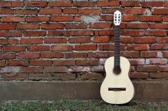 Склонность акустической гитары на кирпичной стене красного цвета grunge Трава на мостоваой Стоковые Фото