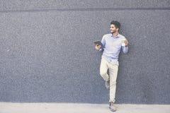 Склонность бизнесмена на стене держа кофейную чашку и используя I стоковое изображение