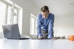Склонность бизнесмена стоящая на его столе читая compu таблетки Стоковое Изображение
