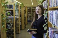 Склонность девушки против книжных полок в библиотеке стоковые фото