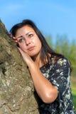 Склонность женщины портрета против ствола дерева Стоковая Фотография RF