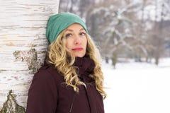 Склонность женщины против дерева в зиме Стоковое Изображение