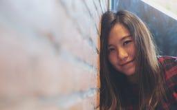 Склонность женщины smiley красивая азиатская на кирпичной стене в современном кафе Стоковые Фотографии RF