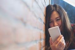Склонность женщины smiley красивая азиатская на кирпичной стене пока использующ и смотрящ умный телефон в современном кафе Стоковое Фото