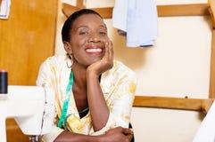 Склонность красивой белошвейки женщины усмехаясь на таблице ее швейной машины стоковое фото rf