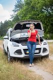 Склонность молодой женщины на сломленном автомобиле в поле и говорить телефоном Стоковые Изображения