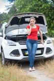 Склонность молодой женщины на сломленном автомобиле с открытым клобуком и вызывать обслуживание помощи автомобиля Стоковые Фото