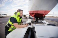 Склонность работника на тележке отбуксировки с самолетом на взлётно-посадочная дорожка Стоковое фото RF