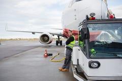 Склонность работника на тележке отбуксировки с самолетом в предпосылке Стоковое Изображение
