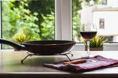 Сковорода и бокал вина тефлона на таблице против окна стоковые изображения rf