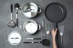 Сковорода удерживания женщины над таблицей с чистым cookware стоковые фотографии rf