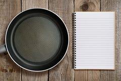 Сковорода и книга рецепта Стоковые Изображения
