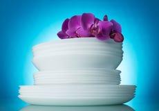 Скольжение чисто помытых белых плит, цветок орхидеи на верхней части, на сини Стоковое Фото